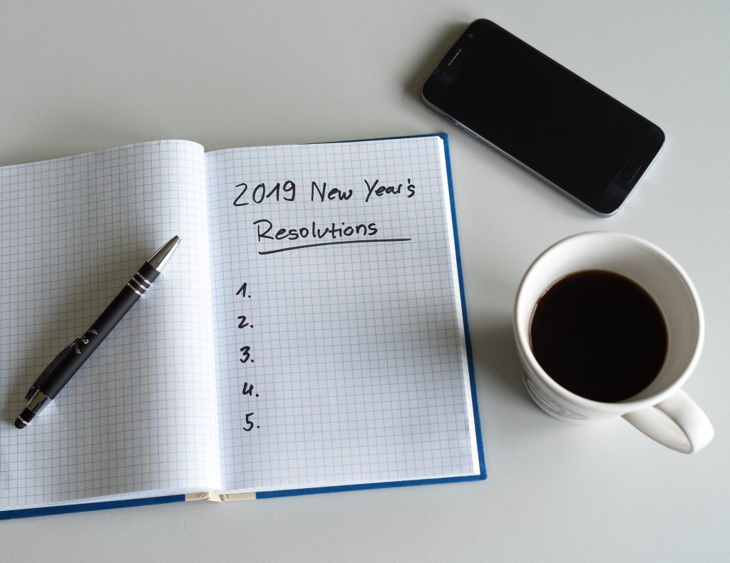 person lacking motivation to start exercise writing down starting exercise as 2019 New Year's Resolution in notebook