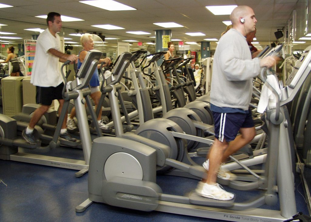 A performance enhancement consultant helping individuals at the gym develop a strong mind to improve their exercise performance on cardio machines