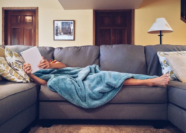 person lacking the motivation to exercise laying on couch with blue blanket covering his body and watching Ipad