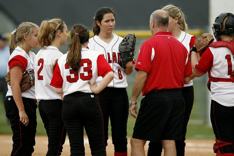 softball coach applying sport psychology techniques such as providing feedback properly during a timeout to help his softball players improve their performance during a game that he learned during a sports performance consulting session with a performance enhancement consultant