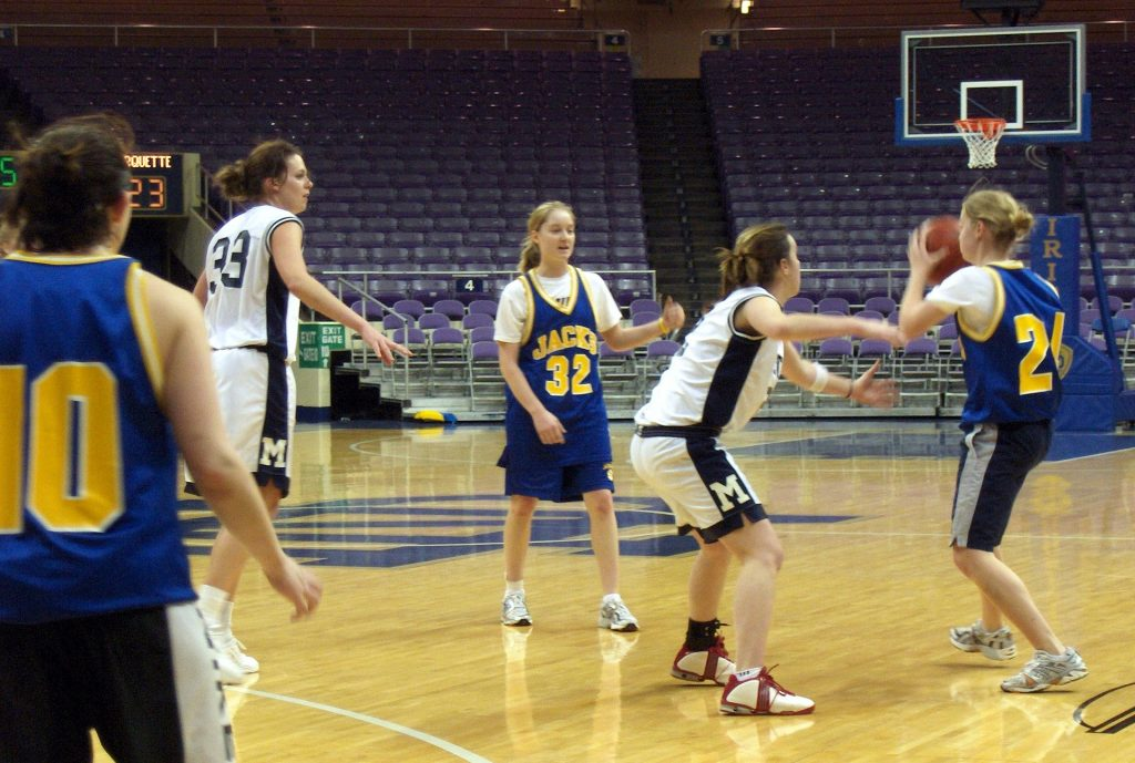 female basketball team using sport psychology techniques such as making practice game like that they learned during a sports performance consulting session with a performance enhancement consultant to develop a strong mindset to help them improve their performance during a competitive game