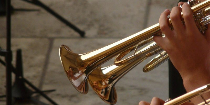 Performance enhancement consultants help individuals in various performance domains improve their performance such as three trumpet players aiming to improve their performance playing the trumpet